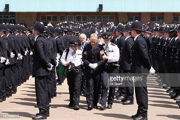 A police officer is helped by colleagues as she becomes faint during a Passing out Parade for the Metropolitan Police at Hendon Police Training...