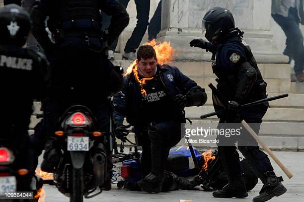 A police officer is helped from his motorcycle after being hit by a petrol bomb as police in full riot gear clash with protesters in front of...