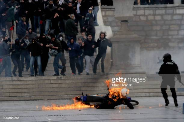 A police officer is hit by a petrol bomb as police in full riot gear clash with protesters in front of parliament in on February 232011 in Athens...