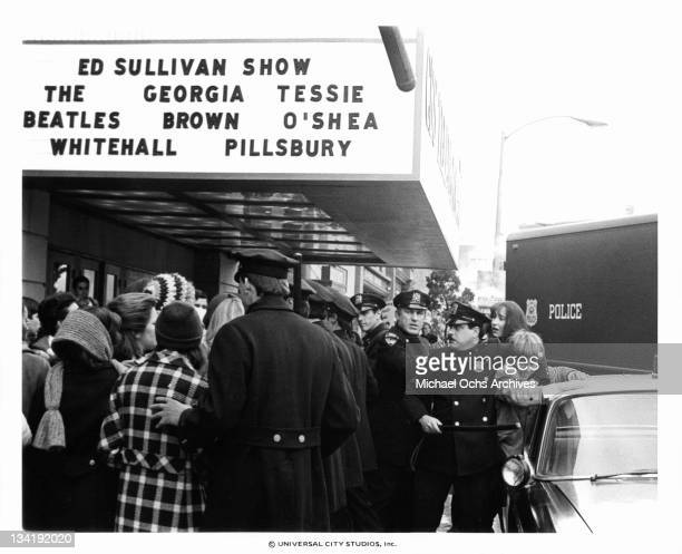 A police officer is restraining Christian Juttner in front of the Ed Sullivan theater where the Beatle will be later in a scene from the film 'I Want...
