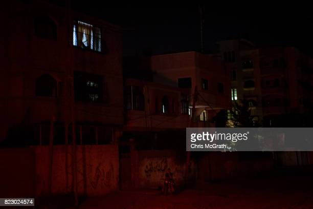 A police officer is seen in the darkness outside apartment blocks on July 20 2017 in Gaza City Gaza For the past ten years Gaza residents have lived...