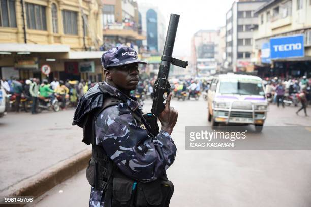 A police officer is seen lifting a teargas launcher opposite protesters during a demonstration on July 11 2018 in Kampala to protest a controversial...