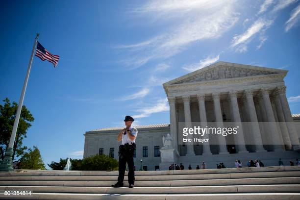 A police officer is seen outside the US Supreme Court after it was announced that the court will allow a limited version of President Donald Trump's...