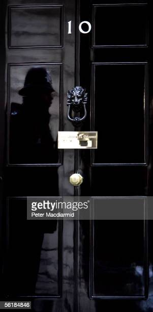 A police officer is seen reflected in the door of number 10 Downing Street before Prime Minister Tony Blair leaves for Parliament on November 16 2005...