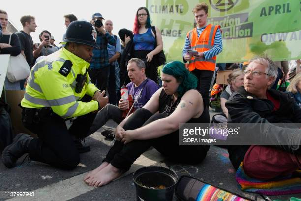 Police officer is seen speaking with an activist during the Extinction Rebellion Strike in London Environmental activists from the Extinction...