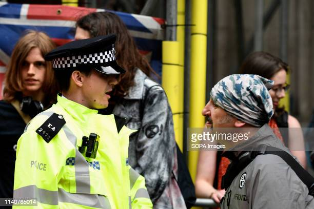 Police officer is seen speaking with an Environmental activists during the protest outside the Brazilian embassy in London Extinction Rebellion...