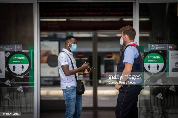 Police officer is seen talking to a man at the train station of Lleida, capital of the Segrià region, on July 6, 2020 in Lleida, Spain. The president...
