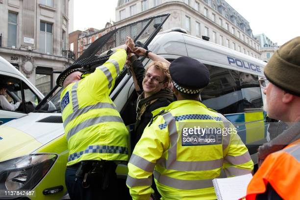 Police officer is seen trying detach a protester who handcuffed himself to a police van during the Extinction Rebellion Strike in London...