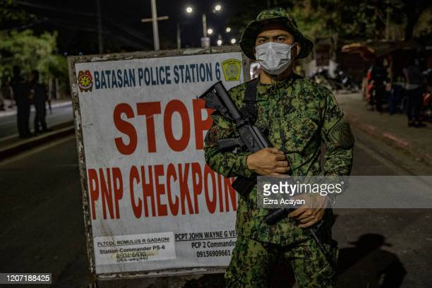 Police officer is seen wearing a facemask as he stands guard at a checkpoint as authorities begin implementing a lockdown on Manila on March 15, 2020...