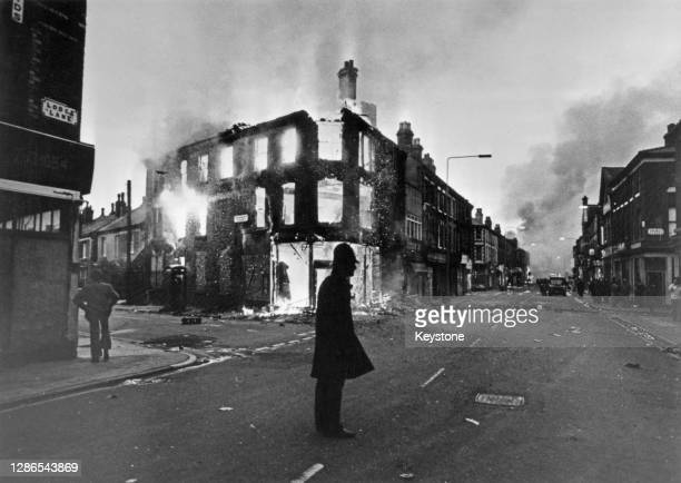 Police officer is silhouetted against a background of a burning building during riots in the Toxteth area of Liverpool, England, 8th July 1981.