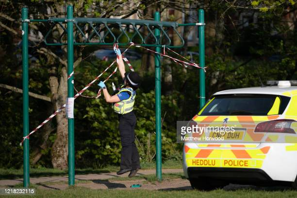 Police officer jumps to puts tape on exercise equipment at Roath recreation ground after a man was seen using the equipment on April 11, 2020 in...