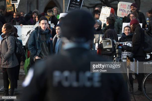 Police officer keeps watch as demonstrators protest a visit by Corey Lewandowski, President Donald Trump's former campaign manager, at the University...