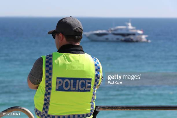 Police officer keeps watch on crowd numbers at Cottesloe Beach on April 10, 2020 in Perth, Australia. Australians have been urged to avoid all...
