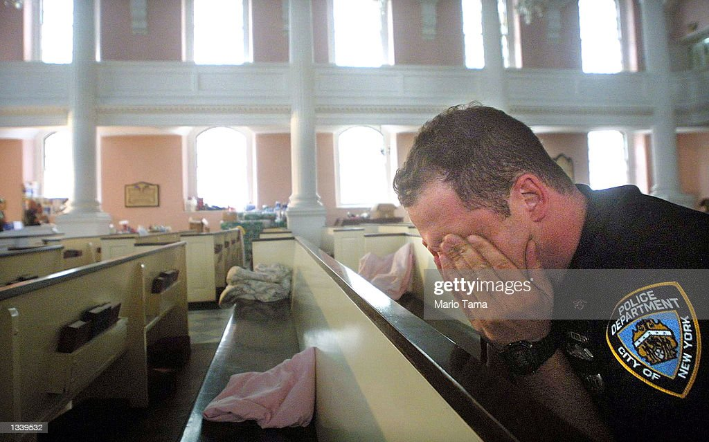 NYPD police officer Ken Radigan rubs his eyes after briefly sleeping in a pew at St. Paul's Episcopal Chapel, near the site of the World Trade Center attack, September 21, 2001 in New York City. The chapel is serving as a relief area for rescue workers.