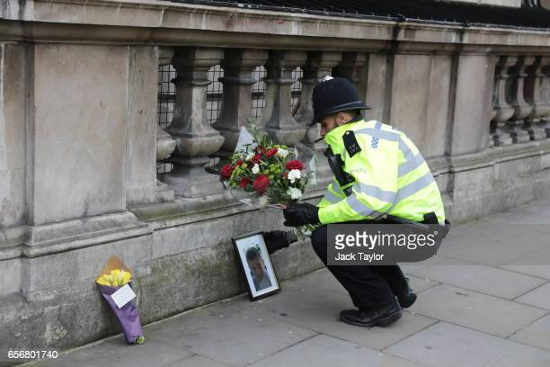 A police officer lays a floral tribute given by a member of the public beside a photo of PC Keith Palmer the policeman who was stabbed to death as he...