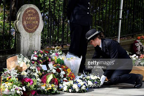 A police officer lays a wreath at the spot where British police officer Yvonne Fletcher was killed during a remembrance service to mark the 30th...