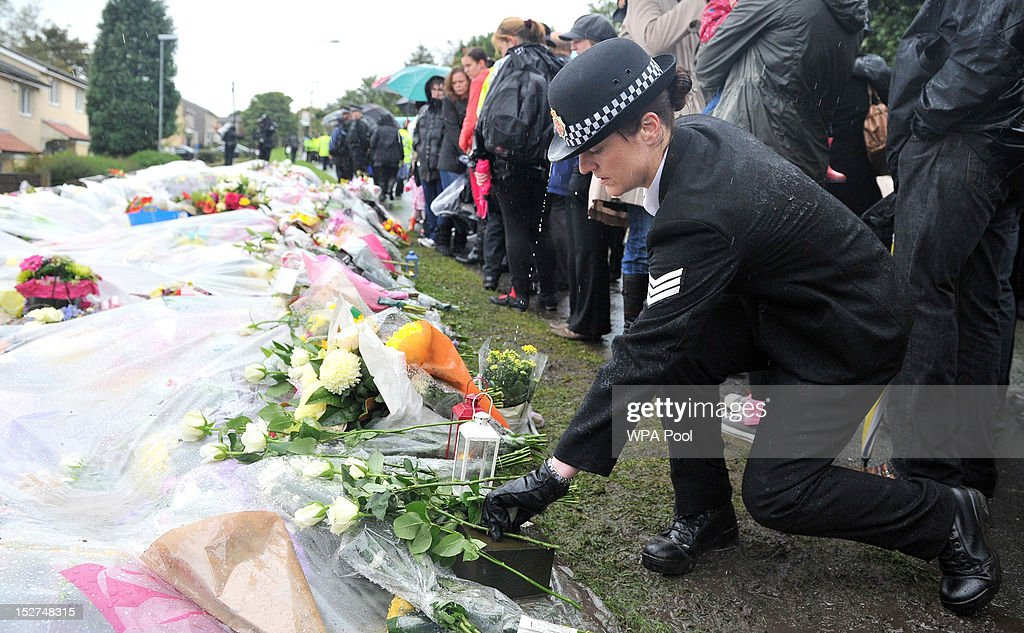 A police officer lays flowers after a vigil near Abbey Gardens for PC Nicola Hughes and PC Fiona Bone, who were murdered one week ago, in Mottram on September 25, 2012 in Manchester, England. Members of the public joined police officers in a walk from Hyde police station to the scene of the killings, for a vigil of prayers and reflection. Dale Cregan, 29, appeared before Manchester Magistrates last week accused of four murders, including those of PC Nicola Hughes and PC Fiona Bone on September 18, and also in two separate attacks earlier this year on Mark Short and his father David Short. Cregan is also being charged with an additional four counts of attempted murder.