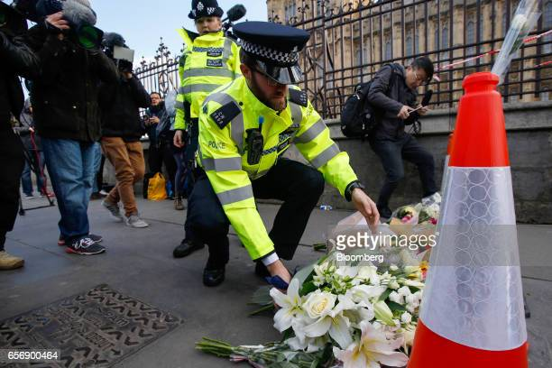 A police officer lays flowers as he pays his respects to the victims of the terror attack outside the Palace of Westminster in central London UK on...