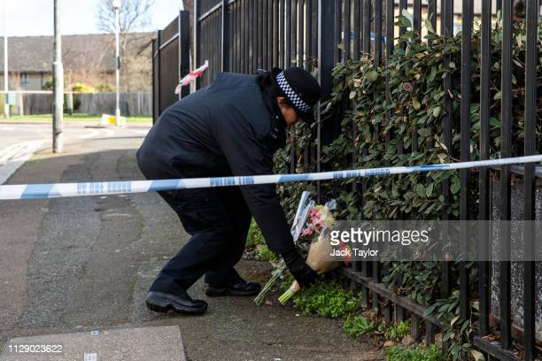 A police officer lays flowers on behalf of a local resident at the scene of a fatal stabbing in Leyton on March 7 2019 in London England A man in his...
