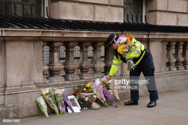 TOPSHOT A police officer lays flowers on Whitehall around a photograph of police officer Keith Palmer who was killed in the March 22 terror attack in...