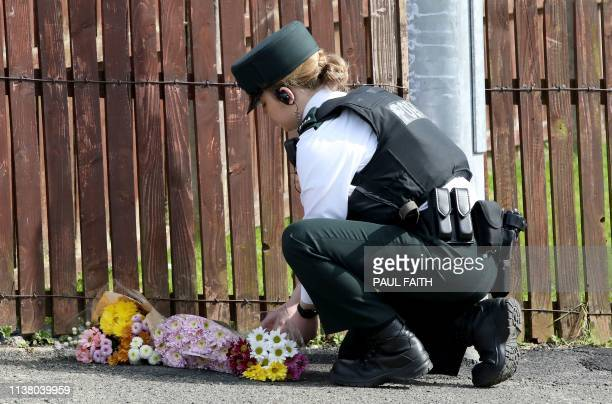 A police officer lays flowers passed to her by members of the public at the scene where a journalist was fatally shot amid rioting overnight in the...