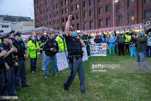 A police officer leads a cheer for healthcare workers at the Westchester Medical Center on April 14 2020 in Valhalla New York First responders from...