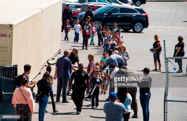 A police officer leads children to be reunited with parents at Cajon High School after a gunman entered a classroom and killed one woman and one...