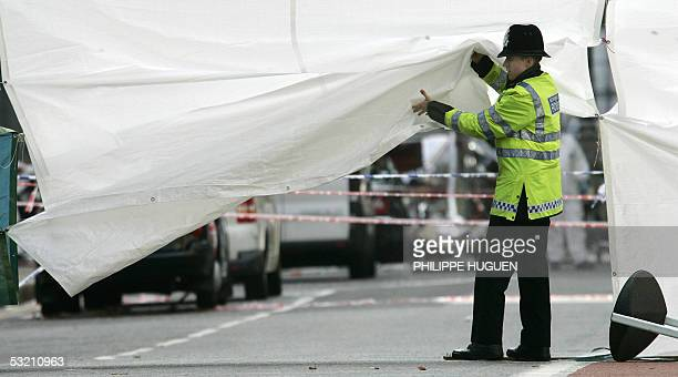 A police officer lifts a screen set up across Upper Woburn Place near Tavistock Square in London 08 July 2005 where a terrorist bomb exploded on a...