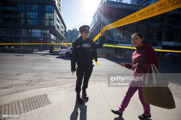 A police officer lifts caution tape for a pedestrian around the scene on Yonge St at near Finch Ave after a van plowed into pedestrians on April 23...