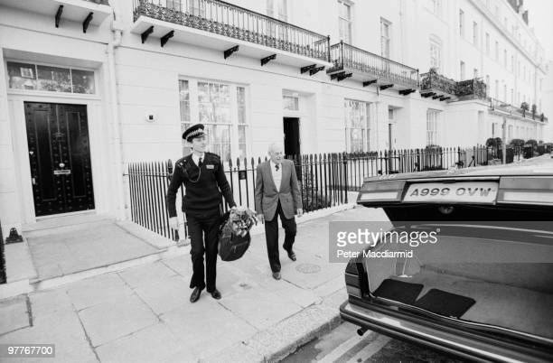A police officer loads a golf bag belonging to Denis Thatcher into a Rolls Royce parked outside the Thatcher's residence in Chester Square London...