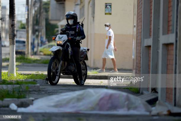 Police officer looks at a body said to be laying for three days outside a closed clinic in Guayaquil, Ecuador on April 3, 2020. - Troops and police...