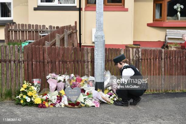 A police officer looks at flowers left in tribute to journalist Lyra McKee near the scene of her shooting on April 19 2019 in Londonderry Northern...