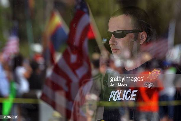 A police officer looks from the Arizona state senate building as demonstrators protest Arizona's new immigration enforcement law during a May Day...
