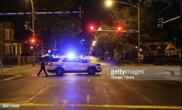 A police officer looks in his patrol SUV trunk while guarding the corner of East 93rd Street and South Jeffery Avenue on Wednesday Sept 27 in Chicago...