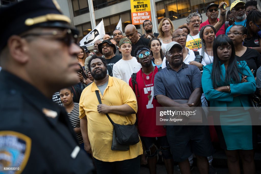 A police officer looks on as activists rally in support of NFL quarterback Colin Kaepernick outside the offices of the National Football League on Park Avenue, August 23, 2017 in New York City. During the NFL season last year, Kaepernick caused controversy by kneeling during the National Anthem at games to protest racial oppression and police brutality. Kaepernick is currently a free agent and some critics and analysts claim NFL teams don't want to sign him due to his public display of his political beliefs.