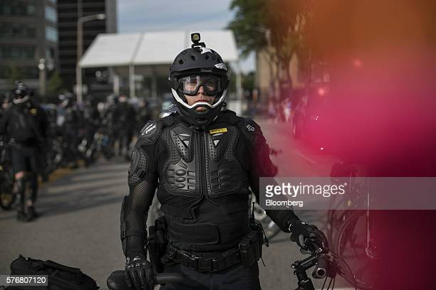 A police officer looks on as protesters march in the street ahead of the Republican National Convention in Cleveland Ohio US on Sunday July 17 2016 A...