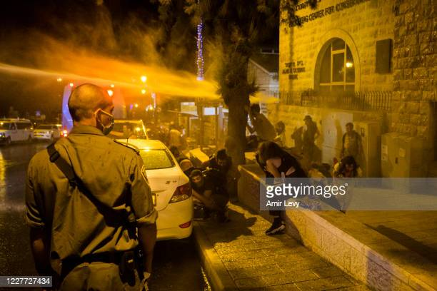 Police officer looks on as water cannons are used to disperse protesters during demonstrations on July 22, 2020 in Jerusalem, Israel. Demonstrations...