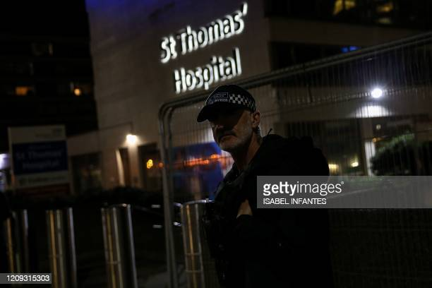A police officer looks on outside St Thomas' Hospital in London late on April 6 2020 British Prime Minister who was diagnosed with coronavirus at the...