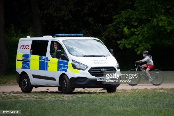 Police officer looks out from a police van in Bute Park during the coronavirus lockdown period as a cyclist passes behind on May 16, 2020 in Cardiff,...