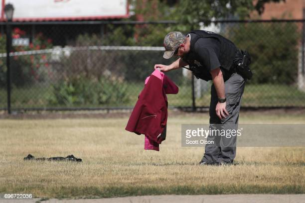 A police officer looks over clothing left behind by children as he investigates a shooting that occurred on the playground at Joseph Warren...