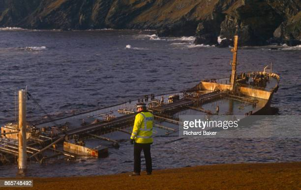 A police officer looks over stormy waves wich crash over the superstructure and funnel of the Liberianregistered MV Braer oil tanker spilling 84700...