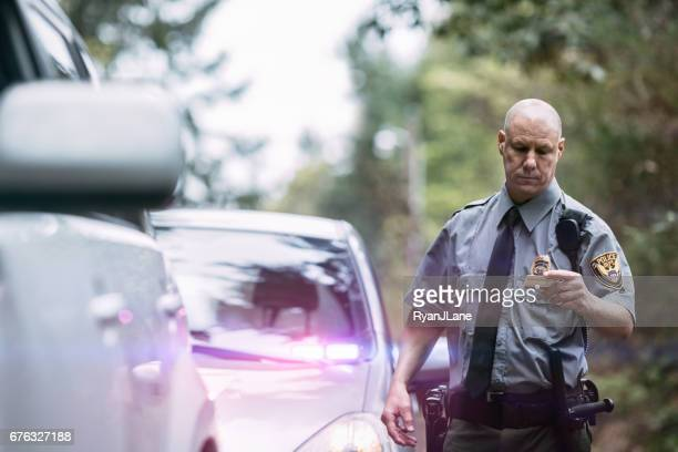 police officer making traffic stop - law enforcement stock photos and pictures