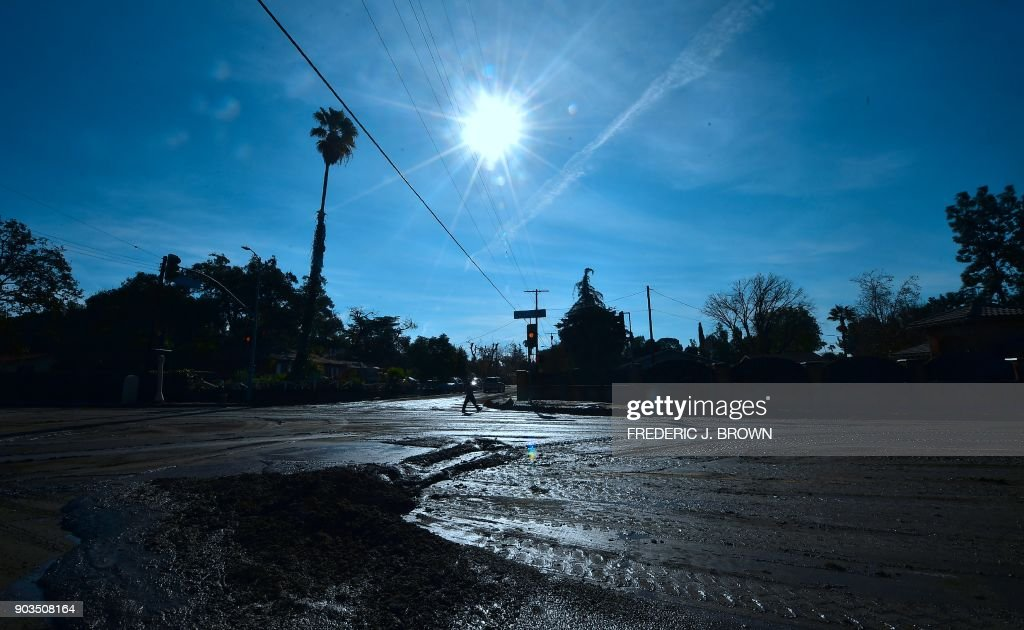 TOPSHOT - A police officer manning a nearby roadblock walks along La Tuna Canyon Road in Sun Valley neighborhood of Los Angeles, California on January 10, 2018. The death toll from devastating mudslides unleashed by a ferocious storm in southern California rose to 15 as rescuers scoured the debris of demolished homes for survivors and bodies. /