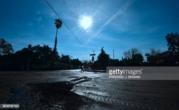 Police officer manning a nearby roadblock walks along La Tuna Canyon Road in Sun Valley neighborhood of Los Angeles, California on January 10, 2018....