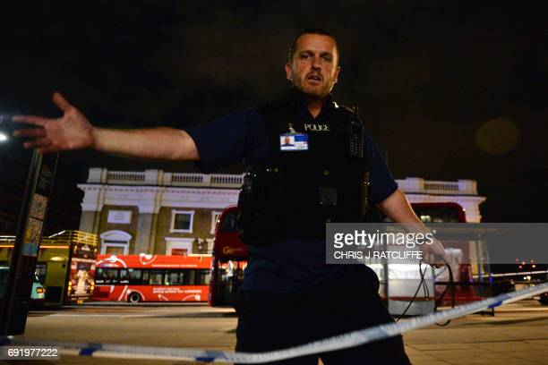A police officer mans a cordon at the scene of a terror attack on London Bridge in central London on June 3 2017 Armed police fired shots after...