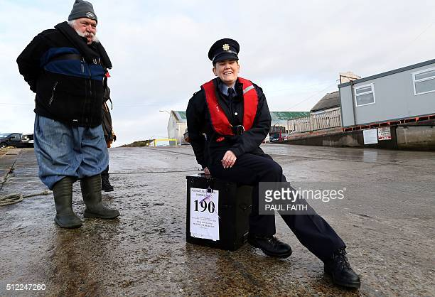 Police officer Margaret Byrne speaks with Inishfree Island resident Hans Schleweck as she prepares to escort a ballot box to Inishfree Island off the...
