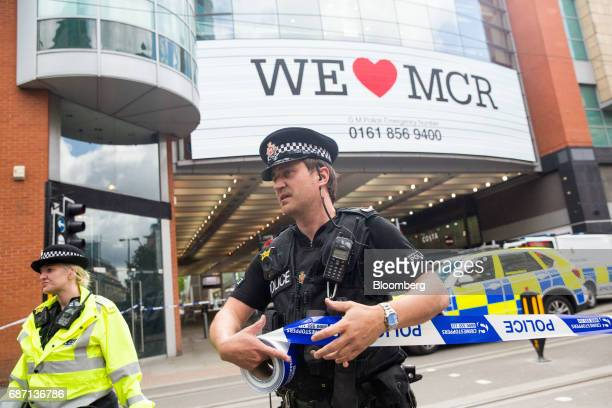 A police officer marks out a cordon using tape following an evacuation at the Arndale shopping mall in Manchester UK on Tuesday May 23 2017 At least...