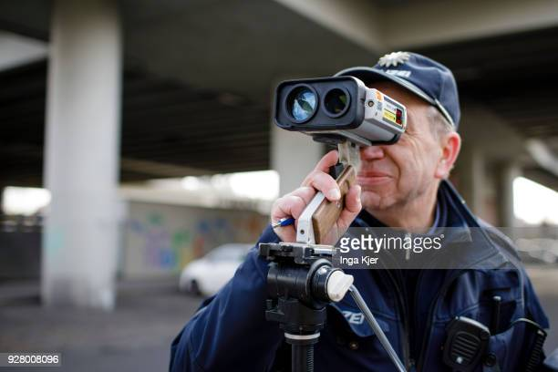 A police officer measures the speed of road users with a speedometer on February 27 2018 in Berlin Germany