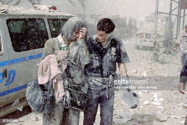 Police officer Mike Brennan helps a distraught woman known only as Beverly, as ash and debris cover the area following the collapse of 1 World Trade...