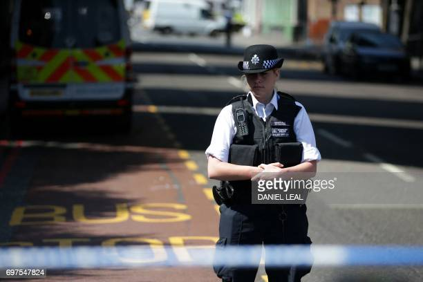 A police officer observes a minutes' silence in memory of the victims of the June 14 Grenfell Tower fire as she stands on duty by a police cordon in...